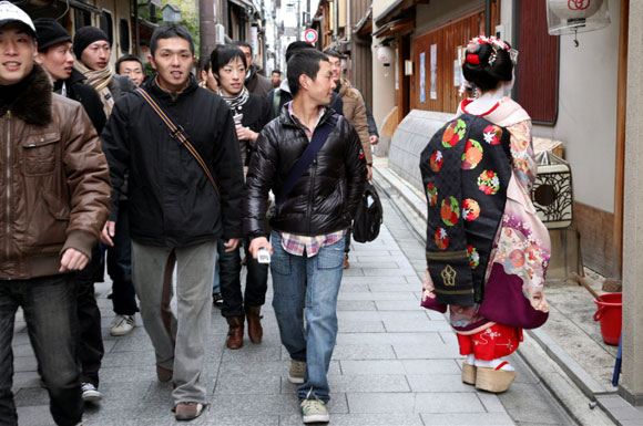Kyoto, una geisha cammina e delle persone vestite all'occidentale la guardano / a geisha walks and people with western clothes look at her