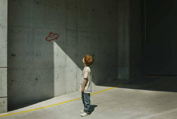 A child watching a UFO drawn on a wall - Un bambino che guarda un UFO disegnato sul muro © Getty Images
