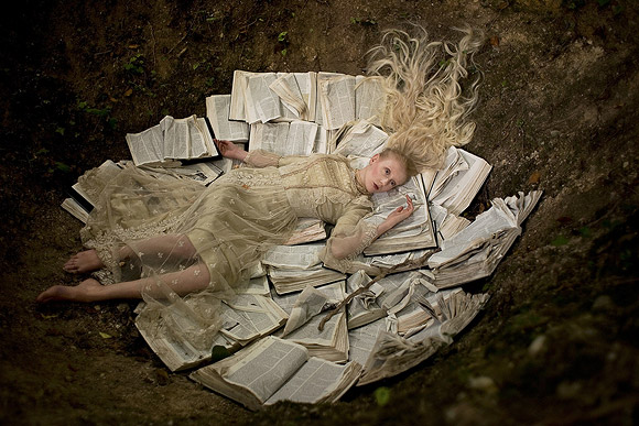 Kirsty Mitchell - 2.. - Ragazza con vestito di pizzo sdraiata sui libri - Girl with lace dress laying on books