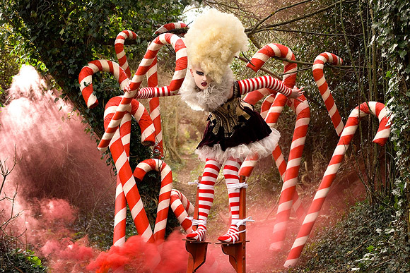 Kirsty Mitchell - 24.......... - ragazza su i trampoli tra i bastoncini di zucchero - girl walking on stilts among candy canes