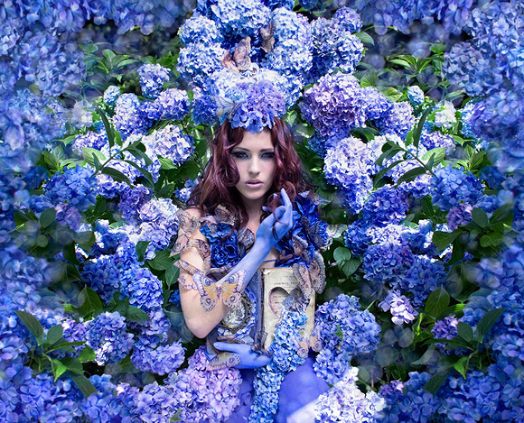 Kirsty Mitchell - 37.......... (The Secret garden) - Ragazza tra le ortensie blu con un libro antico - girl among blu hydrangeas with an old book